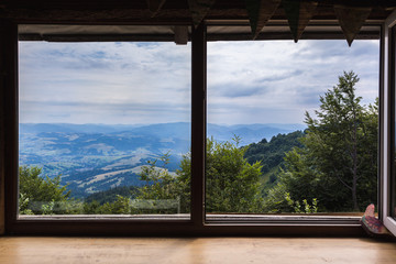 Mountains, view from the window of a wooden house