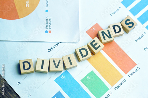 Fotografía  Text DIVIDENDS on wood dice which lay on graph volume document for up trend in stock investment concept