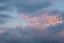 White And Gray Clouds With Pink Sunset Highlights. The Glare Of The Sun On The Clouds. Background.