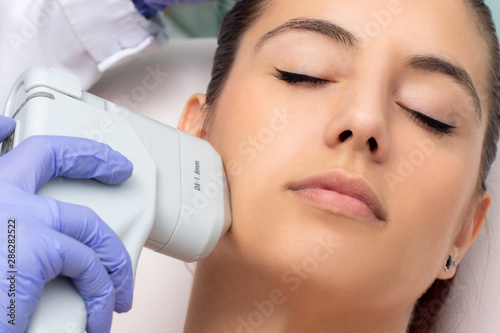 Poster Equestrian Top view of woman having facial hifu energy treatment.