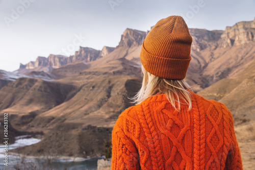 Foto auf Leinwand Lachs Portrait from the back of the girl traveler in an orange sweater and hat in the mountains against the background of a frozen mountain. Photo travel concept