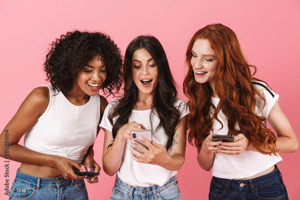 Fototapety, obrazy: Smiling positive young three multiethnic girls friends posing isolated over pink wall background using mobile phones.