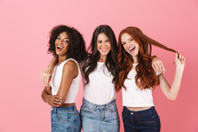 Cheery Smiling Positive Young Three Multiethnic Girls Friends Posing Isolated Over Pink Wall Background.