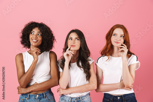 Obraz Thinking thoughtful cute multi-ethnic girls friends posing isolated over pink wall background. - fototapety do salonu