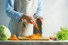 Woman Grates Fresh Carrots For...