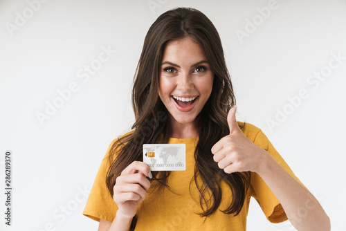 Obraz Image of gorgeous brunette woman wearing casual clothes showing thumb up and holding credit card - fototapety do salonu