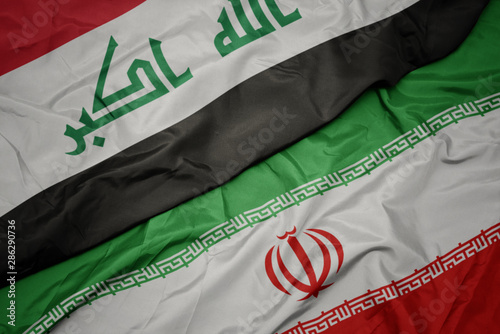 Fotografie, Tablou  waving colorful flag of iran and national flag of iraq.