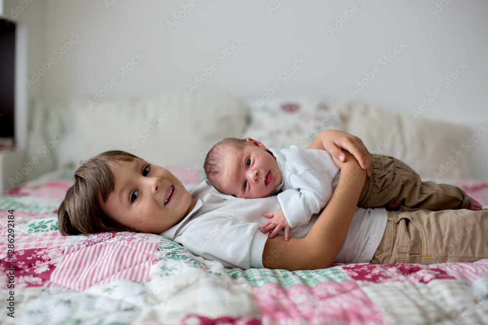 Fototapety, obrazy: Sweet preschool boy, hugging with tenderness and care his little newborn brother