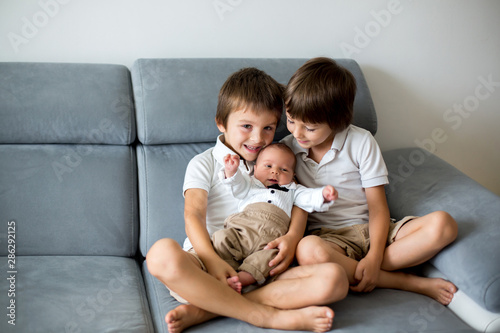 Photo Sweet preschool boys, brothers, hugging with tenderness and care his little newb