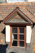 Attic Window On The Roof Of Red Roof Tiles.