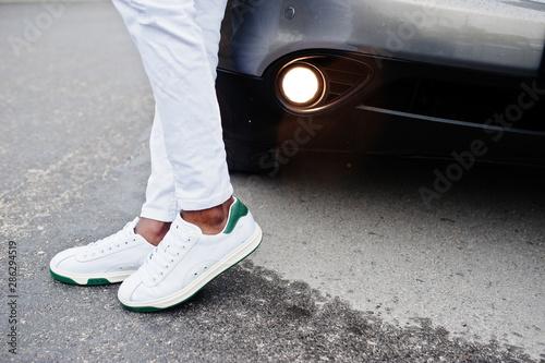 Close up sneakers in african man at white pants against car. Fototapeta