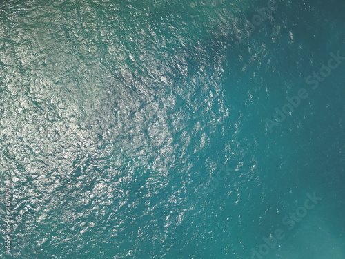 Fototapeta Top View Slow motion looping c ripples and wave, Refraction of sunlight top view texture sea side, Foaming and Splashing in the Ocean, Sunny Day, Slow Motion. Halkidiki, Greece. Veiw from drone obraz