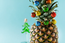 Christmas Tree Made Of Pineapple And Colorful Baubles On Blue Background, Copy Space. Card, Decoration For New Year Party.