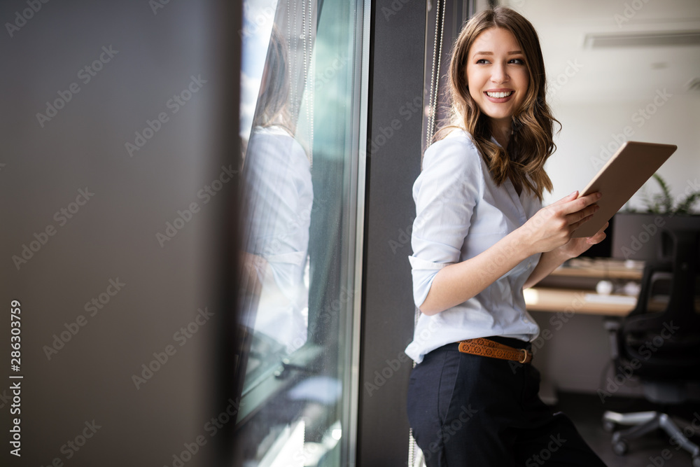 Fototapeta Happy woman manager holding tablet and standing in modern office