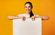 Smiling Girl Holding Empty White Board On Yellow Studio Background