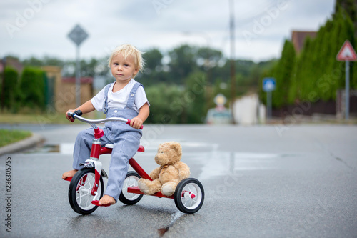 Papel de parede Cute little boy, with teddy bear toy, riding tricycle on the street in the rain,
