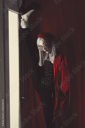 Obraz French girl in red beret with red glasses with heart and big beautiful eyes in an interior loft studio lifts her leg up in standing twine. Woman in red jacket. Fashionable female with white hair - fototapety do salonu