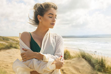 Beautiful Woman Enjoying The Breeze Of The Sea While Walking At The Beach