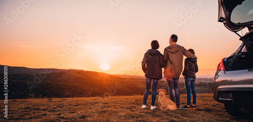 Fotografía  Family with dog embracing at hill and looking at sunset