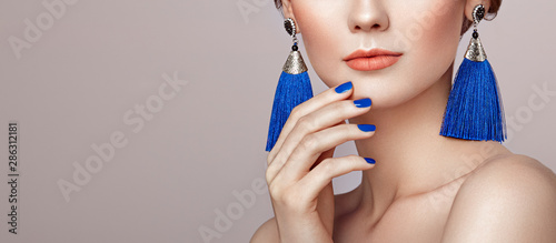 Manicure Beautiful woman with large earrings tassels jewelry blue color. Perfect makeup and nails manicure