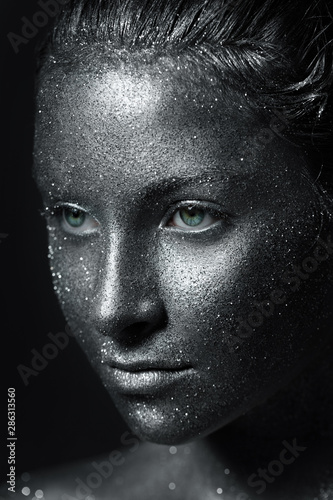 Fototapety, obrazy: the girl's beautiful face is painted silver with sequins. shiny metal powder particles sparkle on the model's face