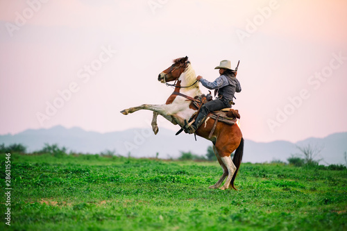 Canvas-taulu cowboy riding horse against sunset