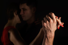 A Man And A Woman Dancing Tango In The Dark; Their Hands Are In Focus And Lit With The Light
