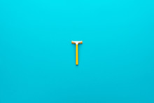 Disposable Razor On The Turquoise Blue Background. Minimalist Photo Of Yellow Plastic Razor With Copy Space