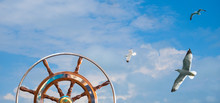 Steering Wheel On Sailing Yacht And Flying Seagulls At Cloudy Sky