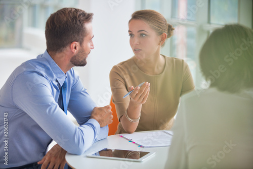 Young colleagues discussing over document at table during meeting in new