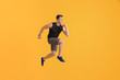 Running young man on color background