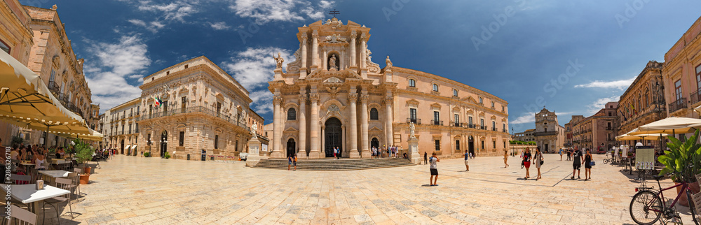 Fototapeta Some tourists are walking admiring the baroque cathedral in the historic center of the island of Ortigia in Syracuse, in Sicily, Italy.