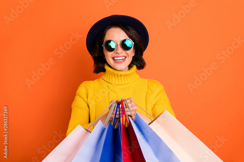 Fototapeta Photo of shopping cheerful girl wearing cap showing you what she has bought while isolated with orange background obraz