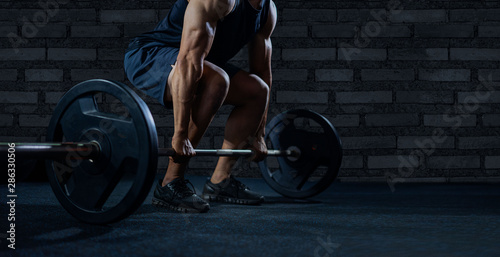 Close up of handsome bodybuilder guy prepare to do exercises with barbell in a gym Fototapeta