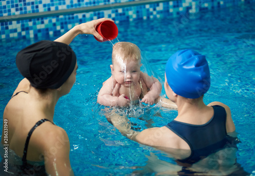 Photo Front view of baby boy during swimming lesson