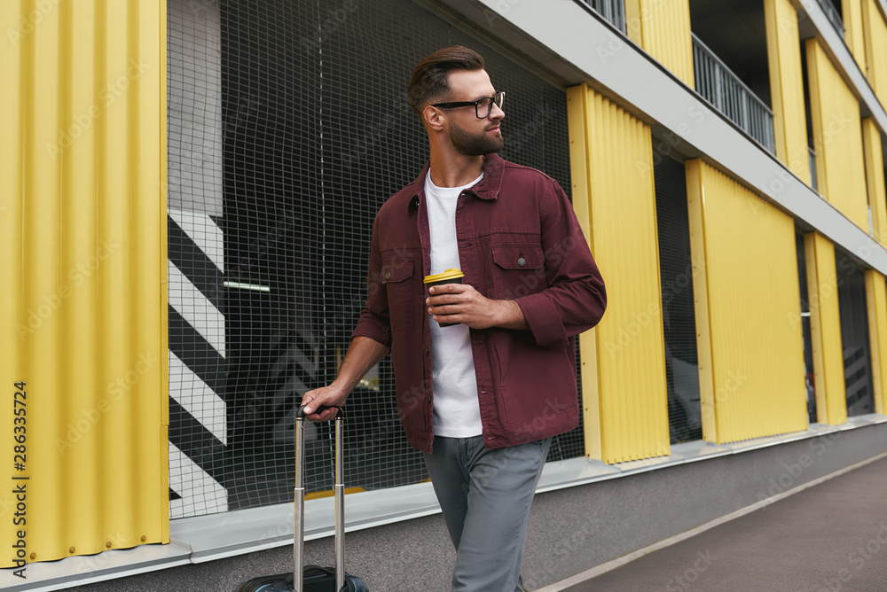 Fototapety, obrazy: Tourist. Handsome bearded man in casual wear and eyeglasses holding a disposable cup and carrying his luggage while walking through the city street