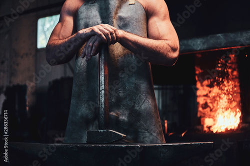 Fotografia Muscular blacksmith in protective apron at his workshop with hammer in his hands