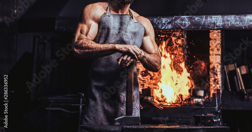 Stampa su Tela Muscular blacksmith in protective apron at his workshop with hammer in his hands