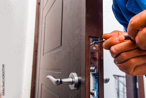 Fotomural  Workman fixing the door lock