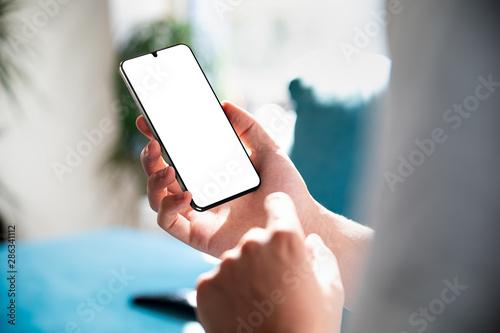 Man using smartphone blank screen frameless modern design while lying on the sof Wallpaper Mural