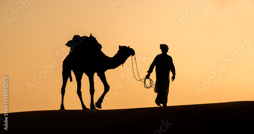Rajasthan travel background - Indian cameleers (camel drivers) with camels silhouettes in dunes of Thar desert on sunset Fototapet