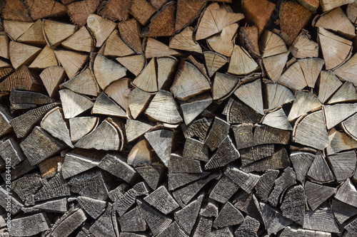Fotobehang Brandhout textuur Background of dry chopped firewood laid in a woodpile. Close-up.