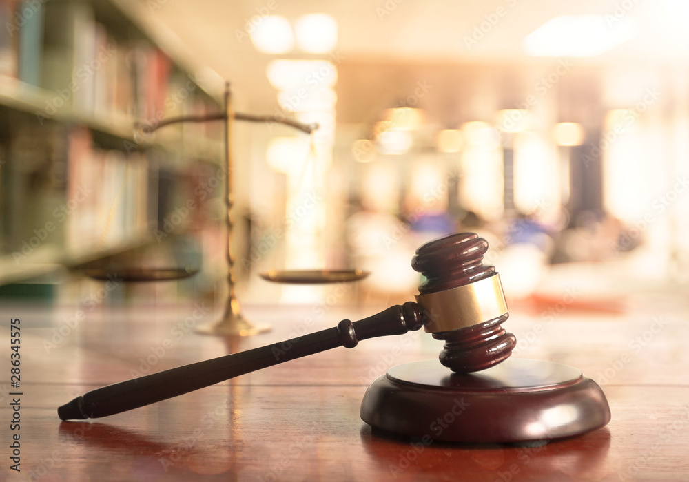 Fototapeta International human rights day concept: Judge gavel with scales on blurred library background