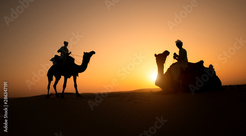 Rajasthan travel background - two indian cameleers (camel drivers) with camels silhouettes in dunes of Thar desert on sunset Canvas-taulu