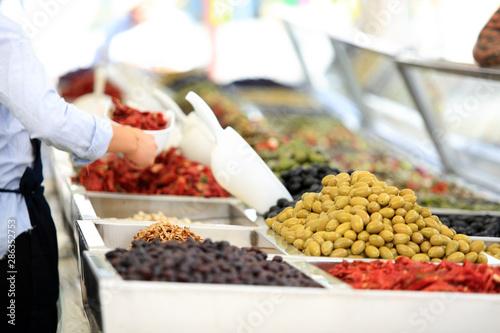 Fototapeta Sprzedawca pakuje oliwki na straganie, w markecie, na rynku miasta Wocław. obraz