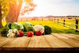 Fototapeta Fototapety do kuchni - Table background with fresh vegetables and sunny autumn view.