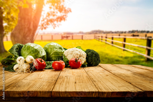 Table background with fresh vegetables and sunny autumn view.