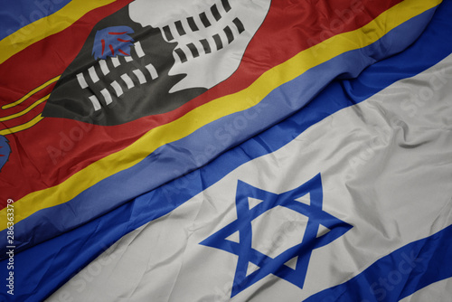 Photo waving colorful flag of israel and national flag of swaziland.