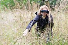 Mature Woman Looks Through Binoculars In High Grass, Bird Watcher, Copy Space