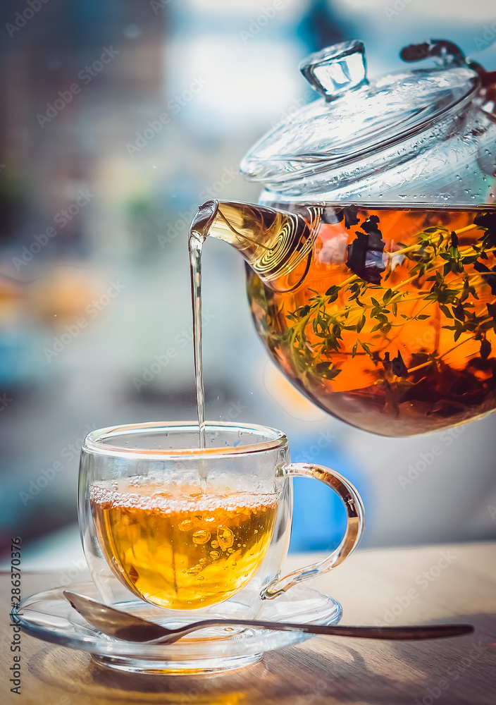 Fototapeta From a glass kettle pour tea into a glass cup on a light background
